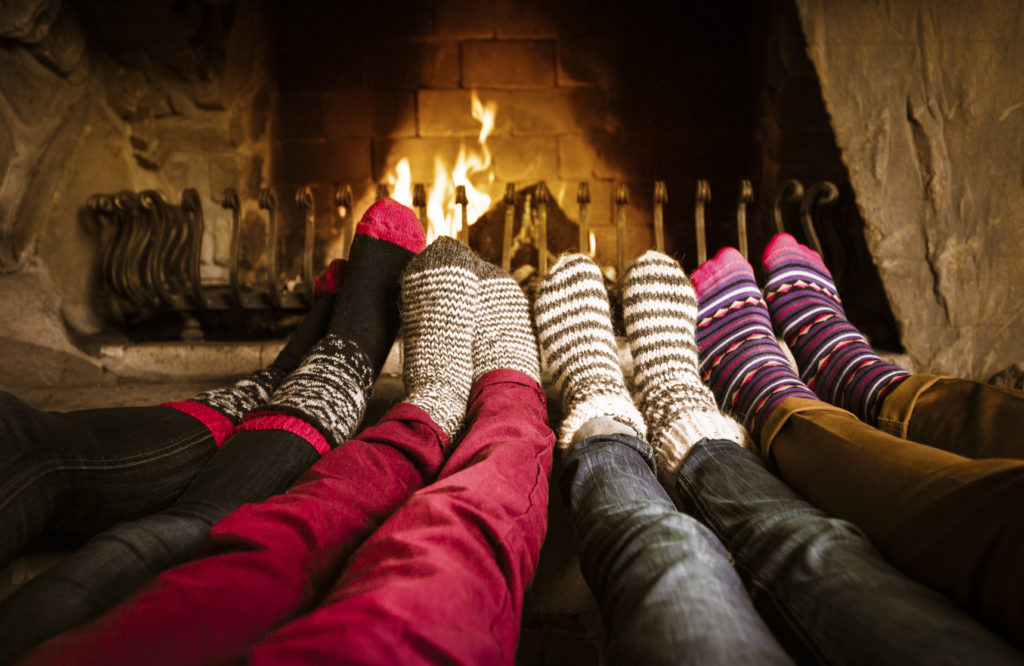 Four people warming their feet by the fireplace.